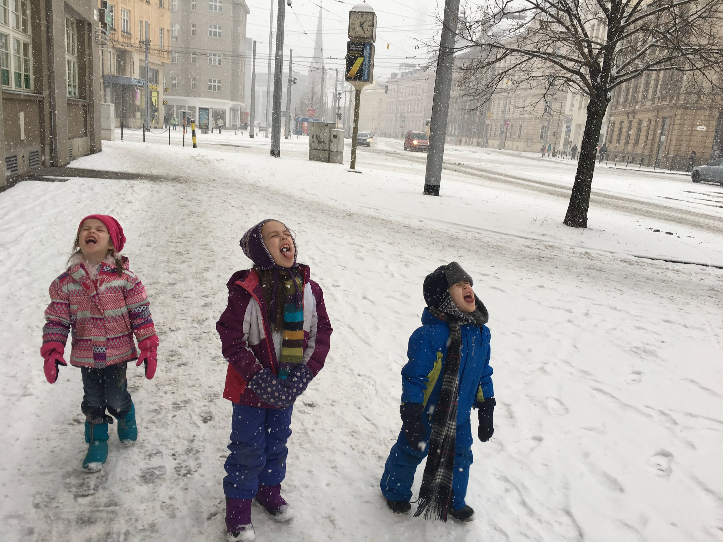 The kids catching snowflakes while walking downtown.