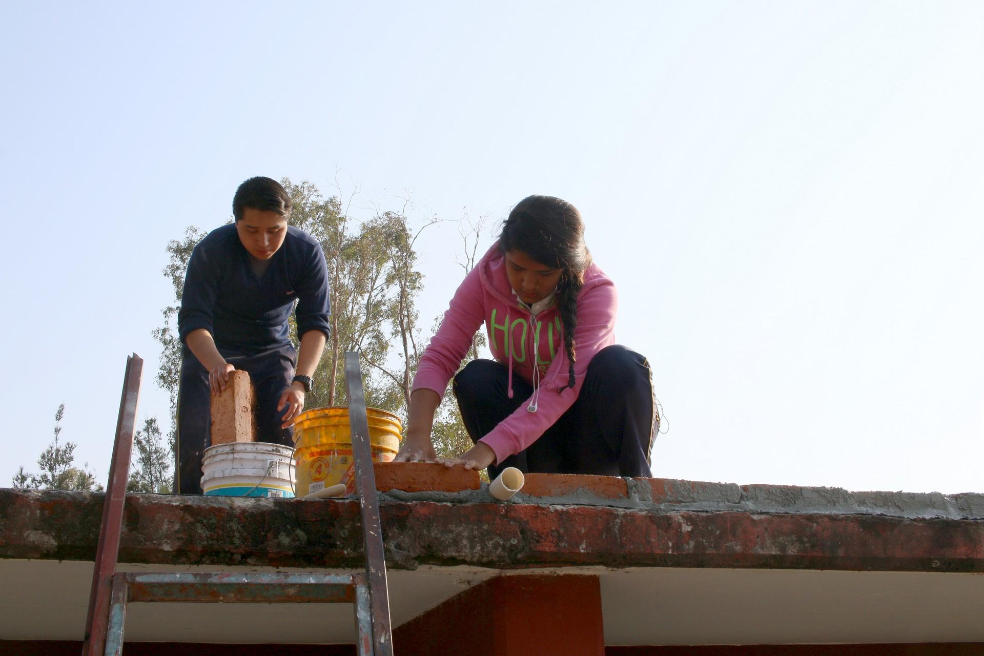 Dos estudiantes ponen ladrillos en el techo que formarán la canalización a las tuberías.