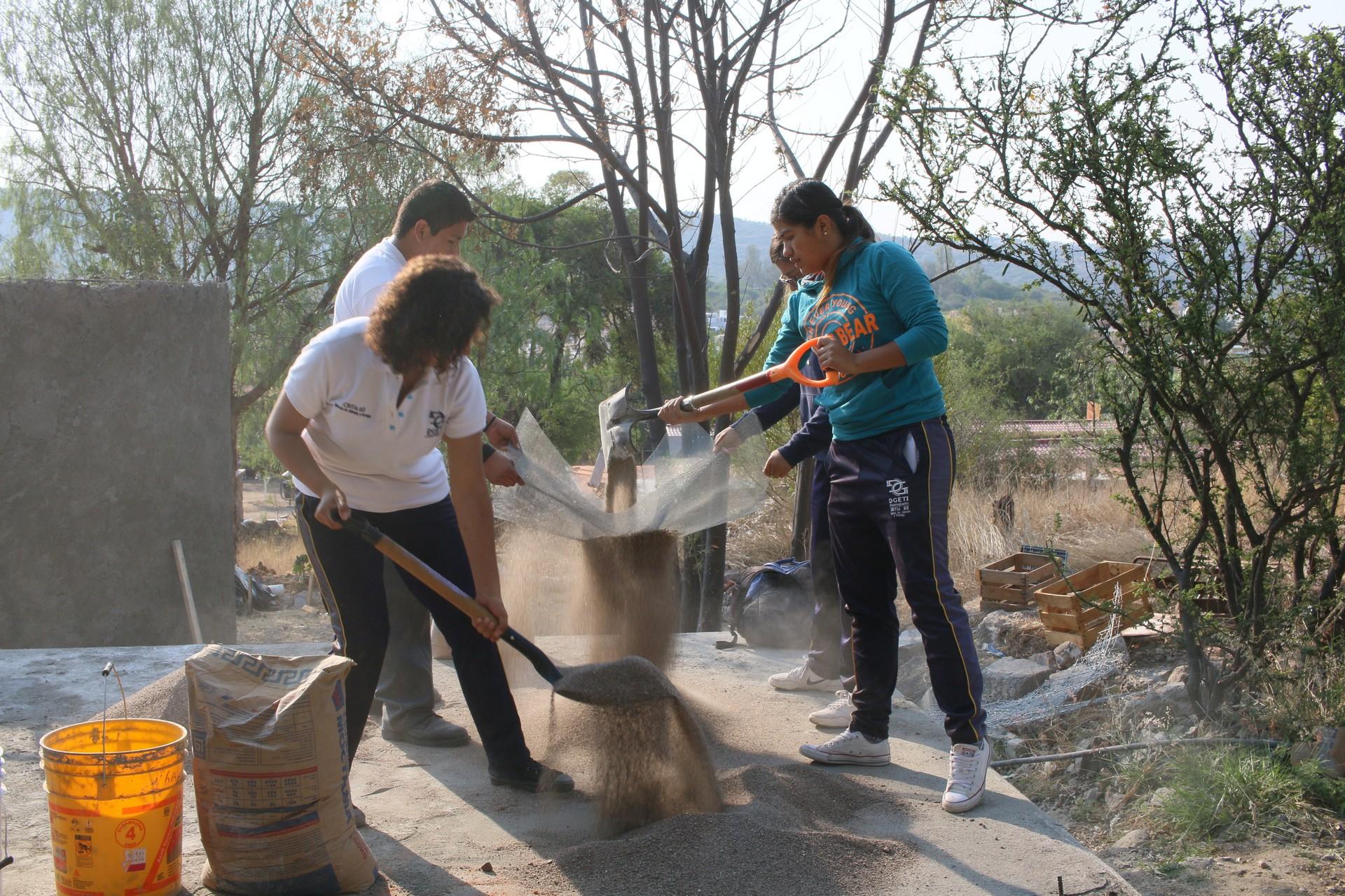 Los estudiantes criban la arena para la mezcla de cemento.