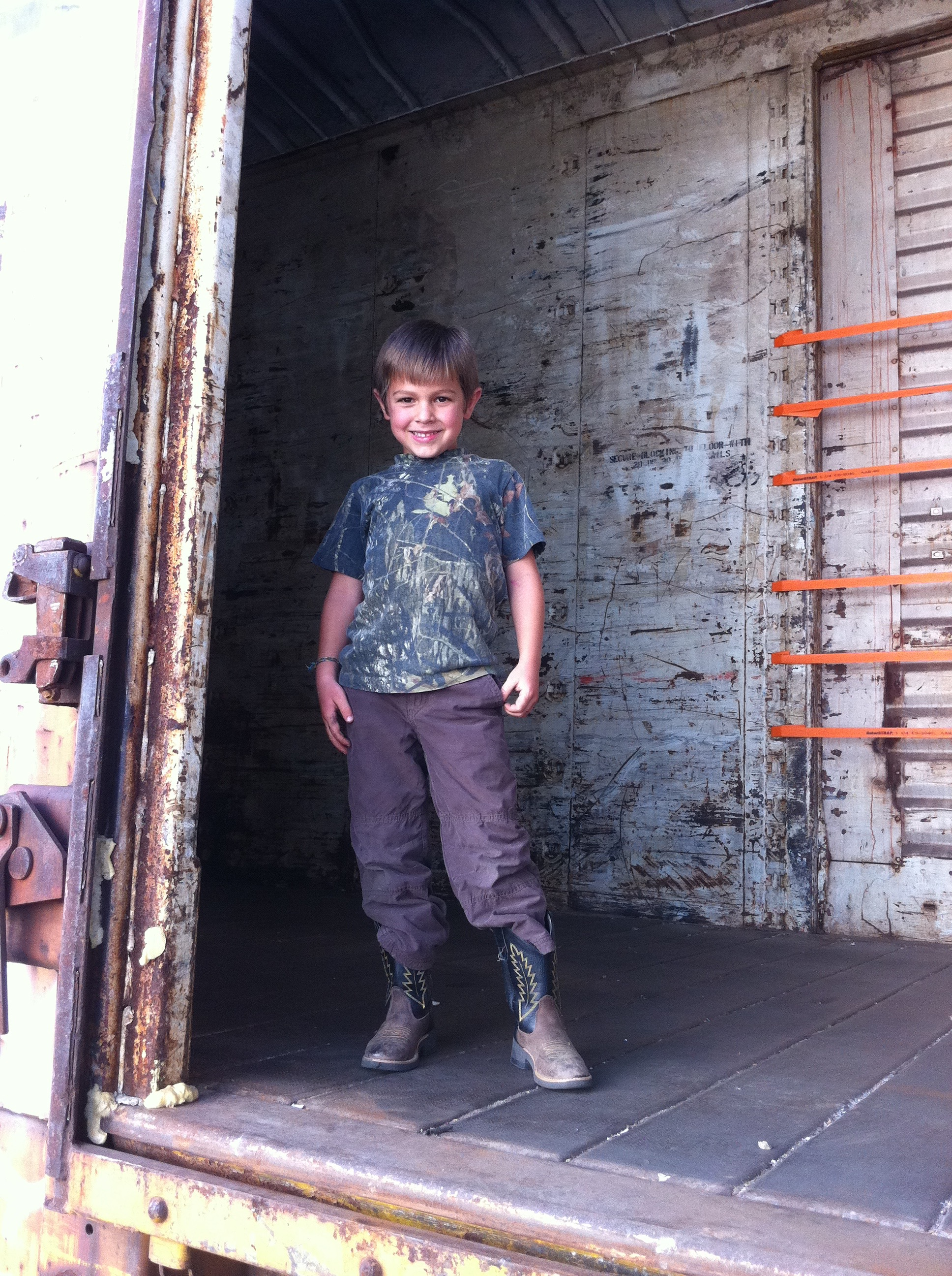 my son in an empty train car that is waiting to be loaded with cotton seed