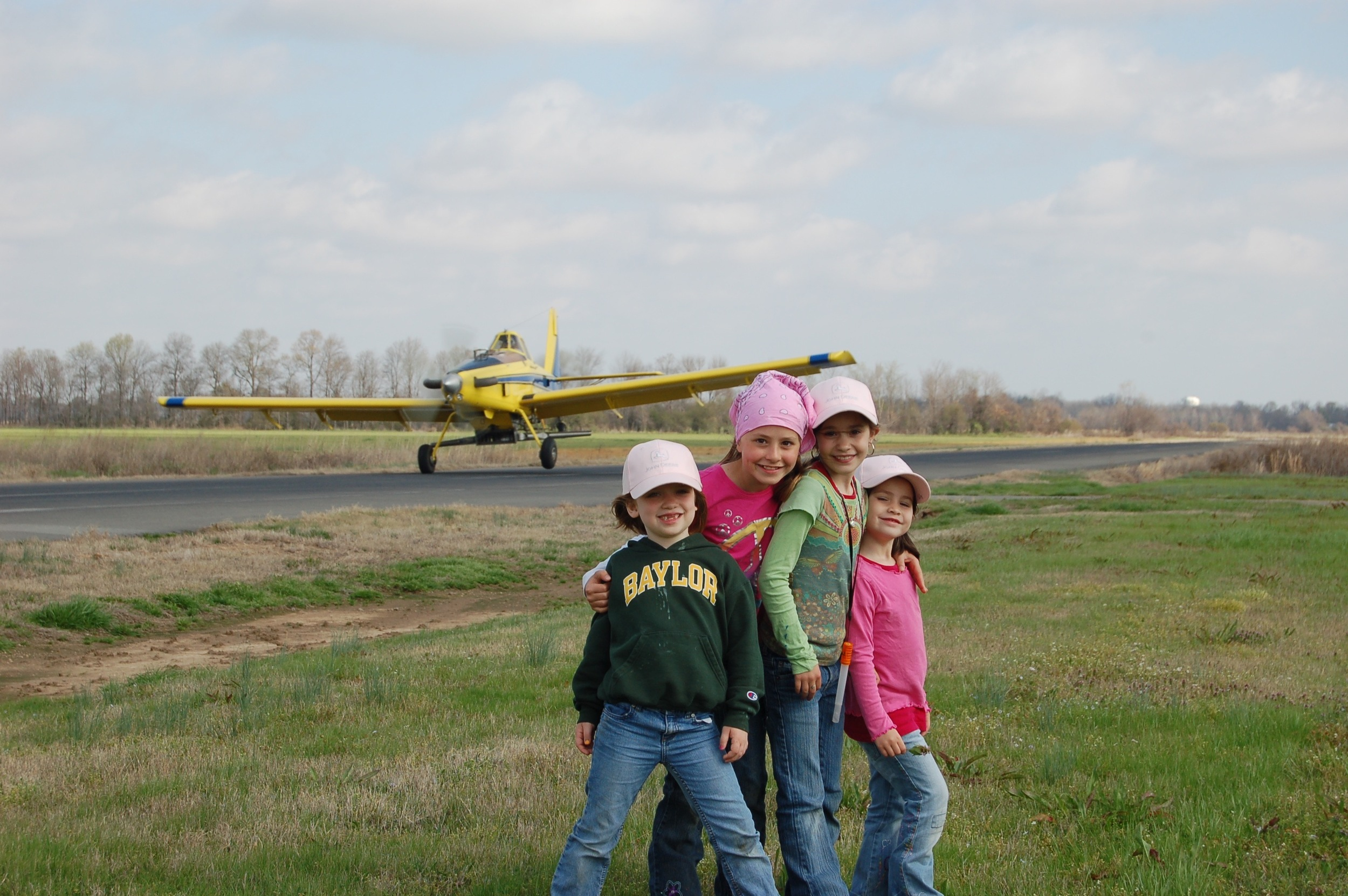 friends posing with the airplane as it loudly takes off