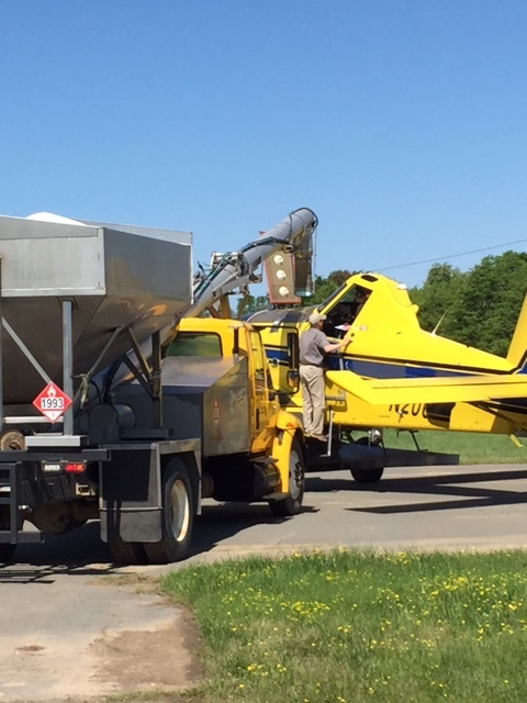 a carefully measured application being loaded into an ag plane