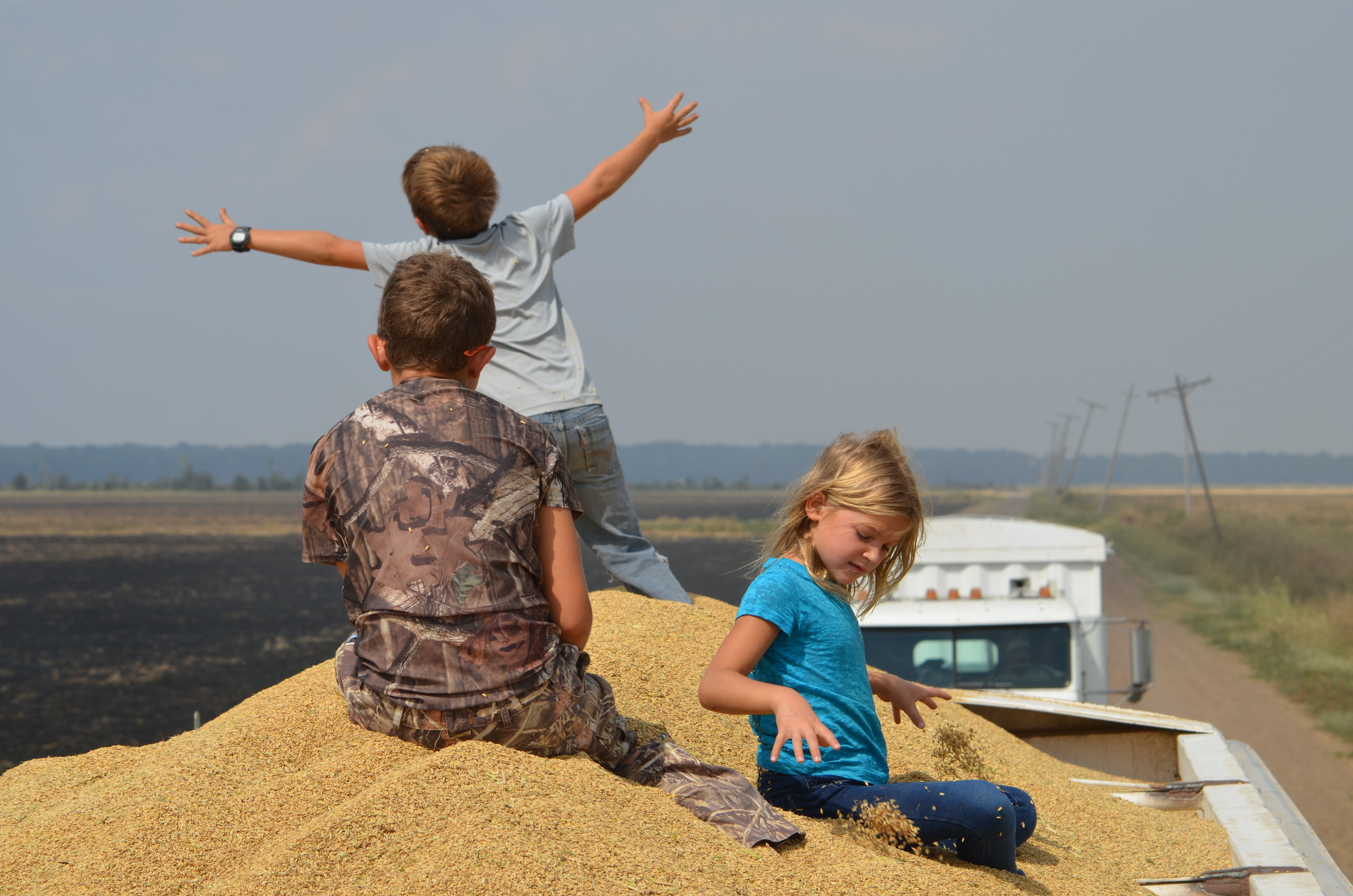 kids playing on a truck full of harvested rice