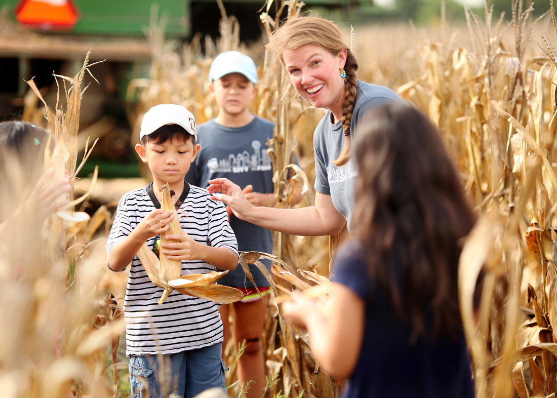 Executive Director Kris Habashy helps students from the DFW area shuck field corn and explore the difference between what is in the field and what is bought in a grocery store.