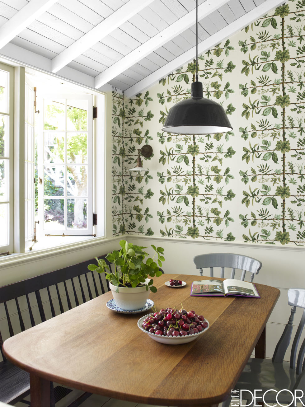 Traditional elements like the farmhouse chairs and botanical wallpaper from iconic French home furnishings company  Pierre Frey keep the breakfast nook homely. High-gloss paint and an industrial light pendent keep it looking youthful.