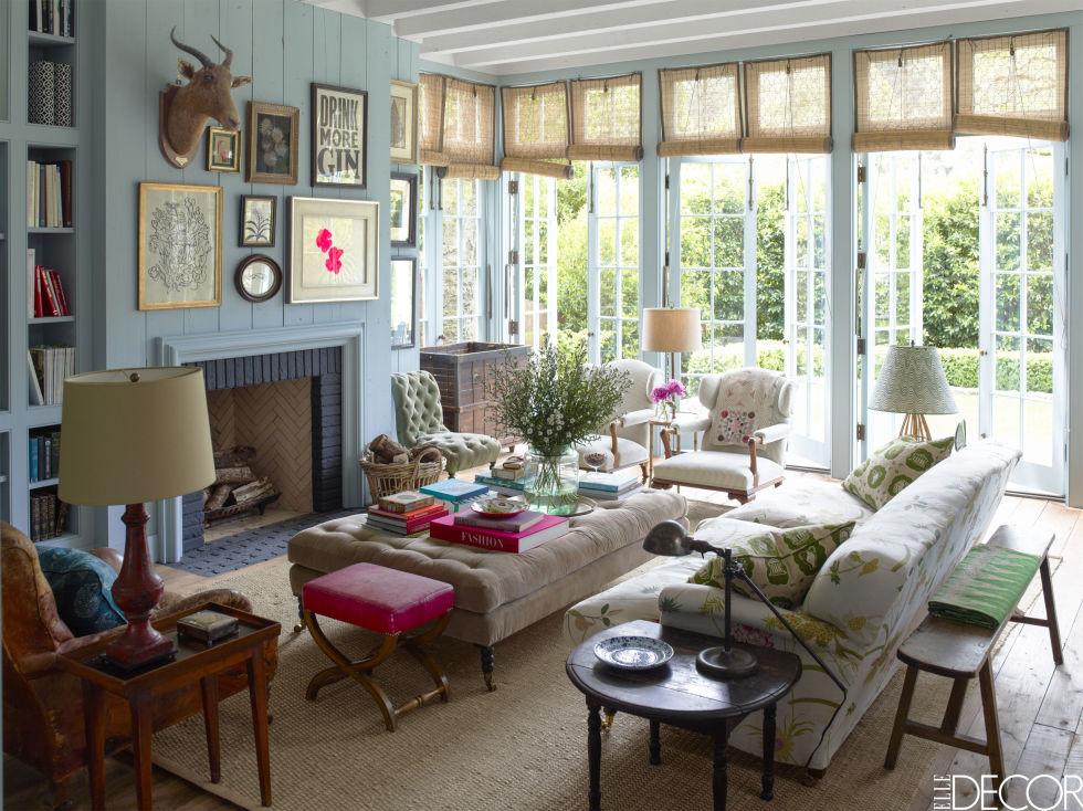 A traditional sofa was reupholstered in floral  Raoul textiles and along is one of many neutral-coloured seating options in the family room. A fuchsia stool and punchy throw pillows prevent the look from being too dull. As a result, the overall feeling is colourful and vibrant.