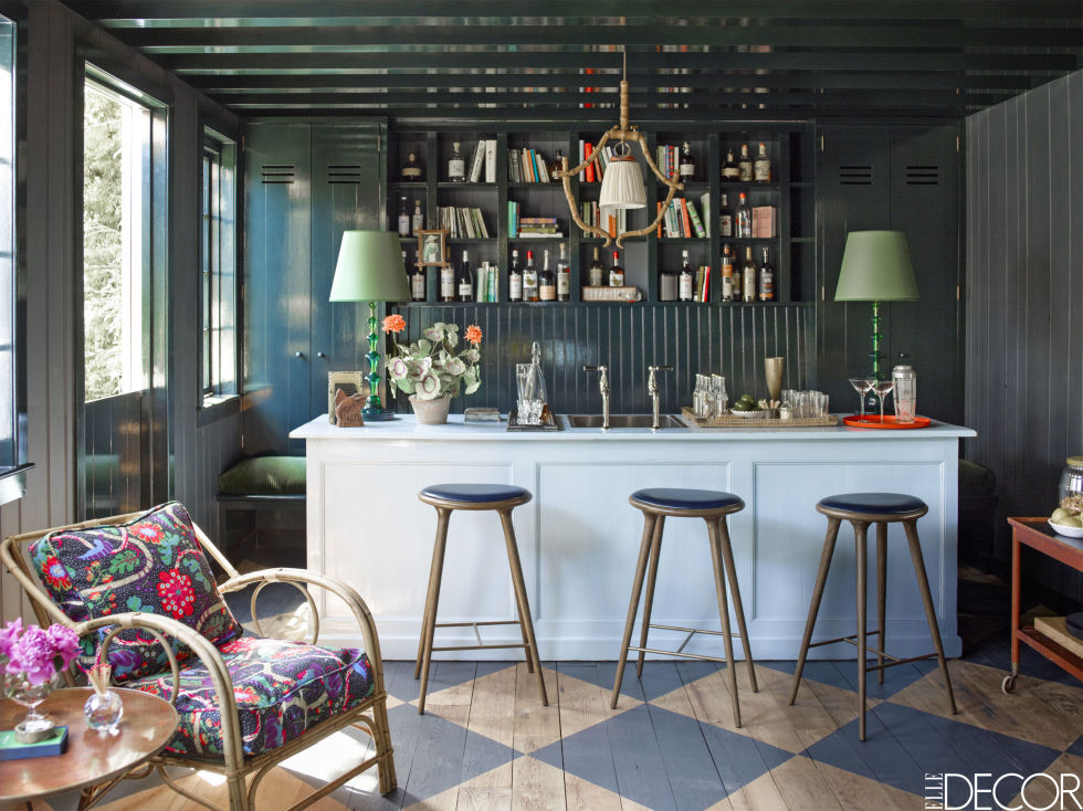 Contemporary  Julian Chichester  bar stools line a vintage bar, creating the perfect space for home entertaining. The cane armchair was found in a flea market and reupholstered in fabric by Austrian architect Josef Frank .