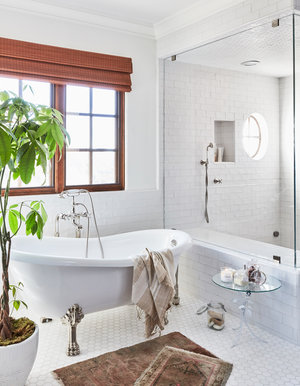 I love the use of vintage Persian rugs in place of bathmats. They compliment the traditional clawfoot tub's romantic feel. -