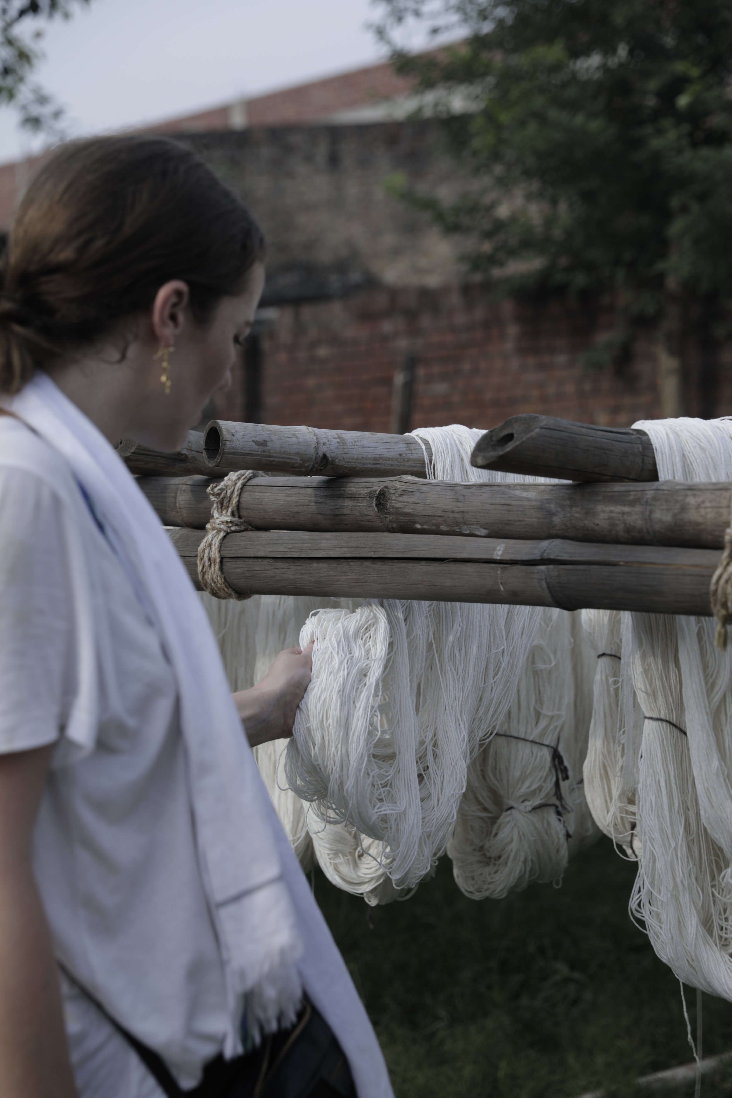 Founder, Olivia Smith, in India checking the yarn quality drying in the sun