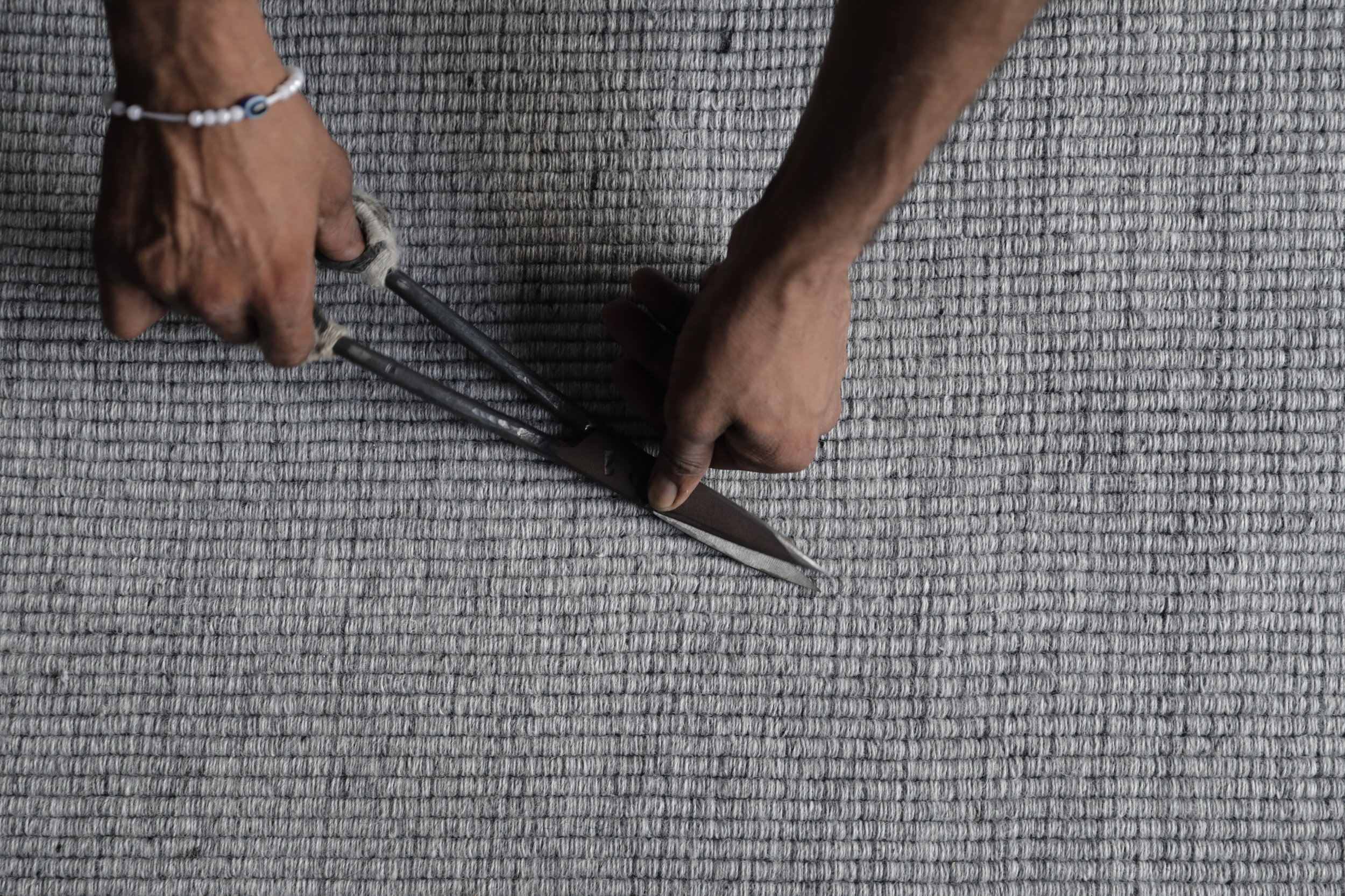 Adding the finishing touches to the Ribbed Wool rug