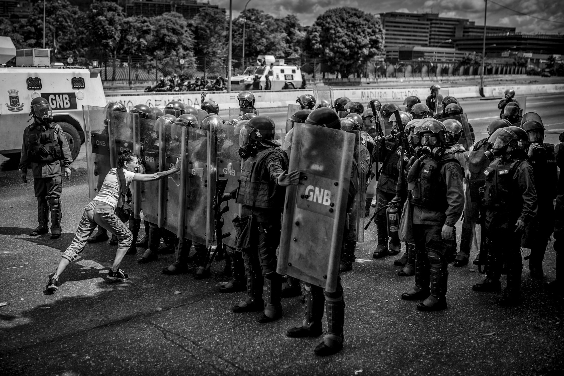 A woman tries to stop National Guard anti-riot officers during an anti-government protest, in 2017.   Photographs by Alejandro Cegarra .