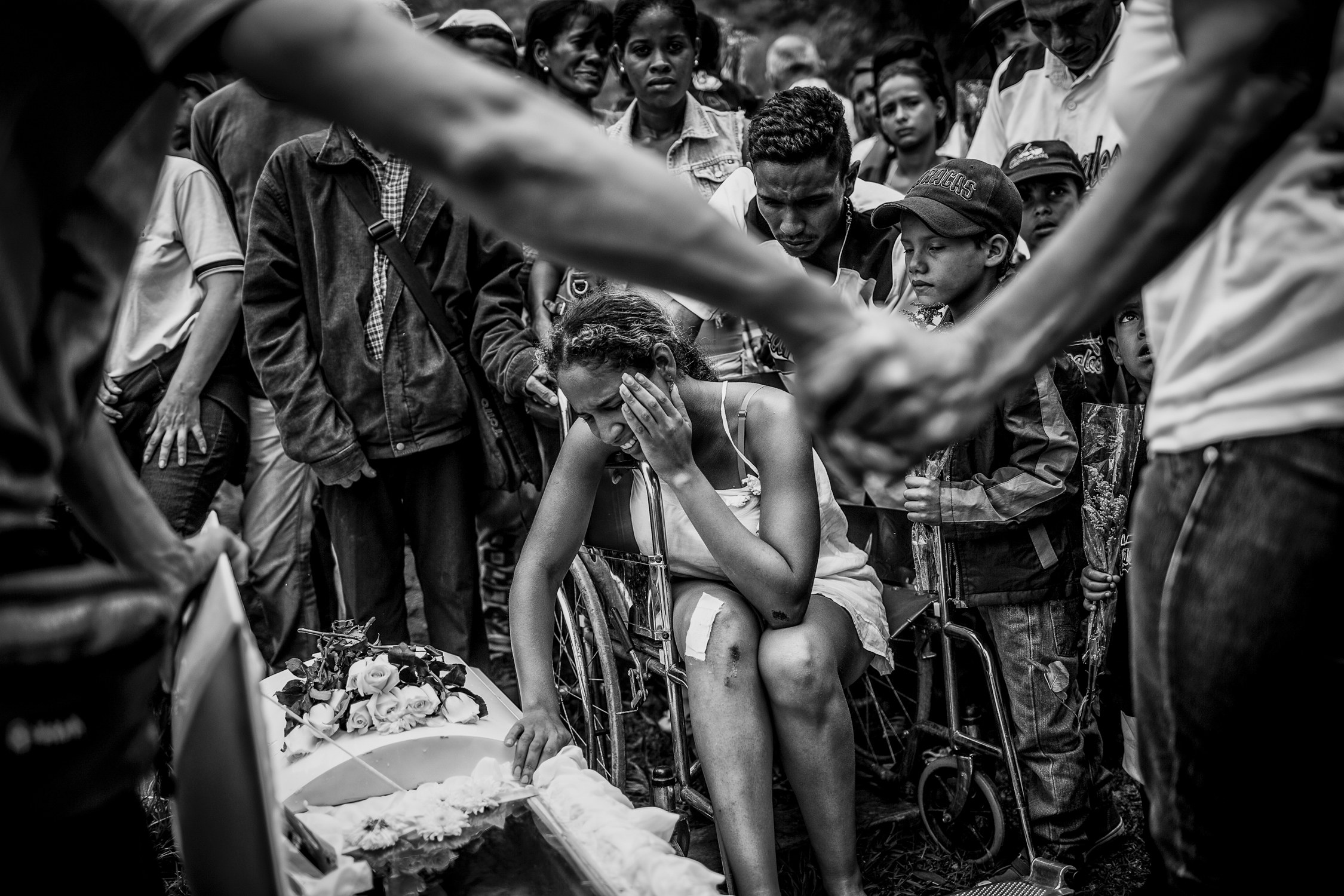 Maria Vizcaya cries over the coffin of her five-year-old son, Gabriel Vizcaya, who died from the shock wave caused by a grenade thrown during a confrontation between police officers and gang members, in 2016 .  Photographs by Alejandro Cegarra .