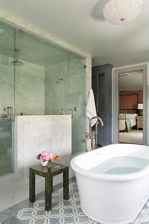 An oval freestanding bathtub paired with a floor-mount tub filler as well as a malachite accent table sits atop a blue geometric tiled floor. A freestanding bathtub is placed in front of a seamless glass and marble walk-in steam shower fitted with his and hers shower heads.