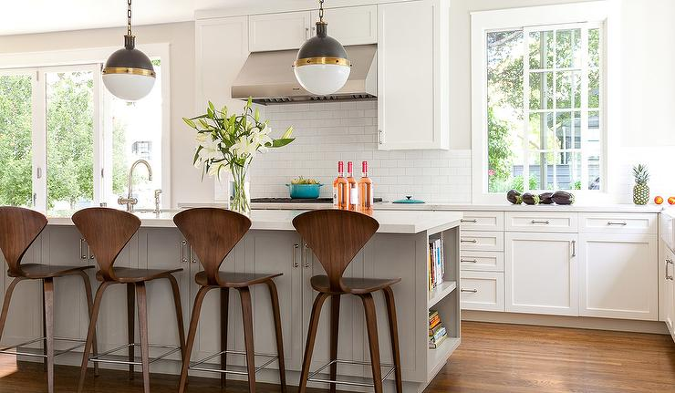 Center stage in this kitchen with a gray kitchen island are Cherner Counter Stools. This Lovely kitchen A pair of Thomas O'Brien Bryant Sconces illuminate over the clean simple style kitchen island by Grant K. Gibson .