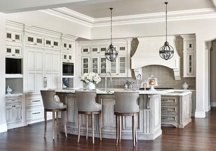 Glamorous, kitchen white marble countertops swivel seating three gray leather bar stools facing a second island..   Less
