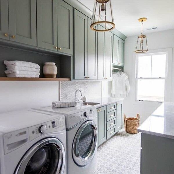 Green gray laundry room is lit by a brass and glass lantern hung in front of green gray shaker cabinets by  MAWR Architecture