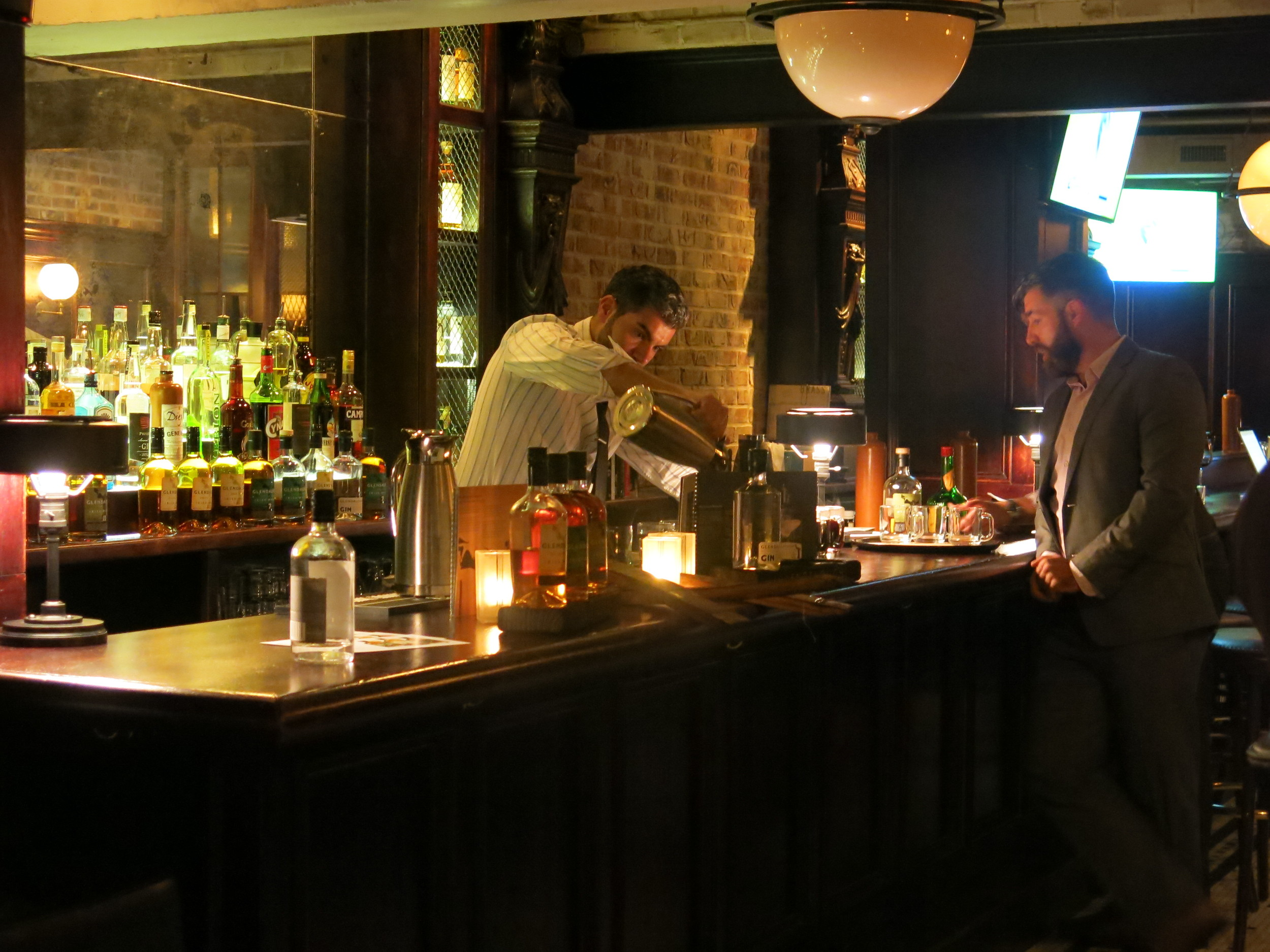Paulo whips up drinks while Donal looks on.