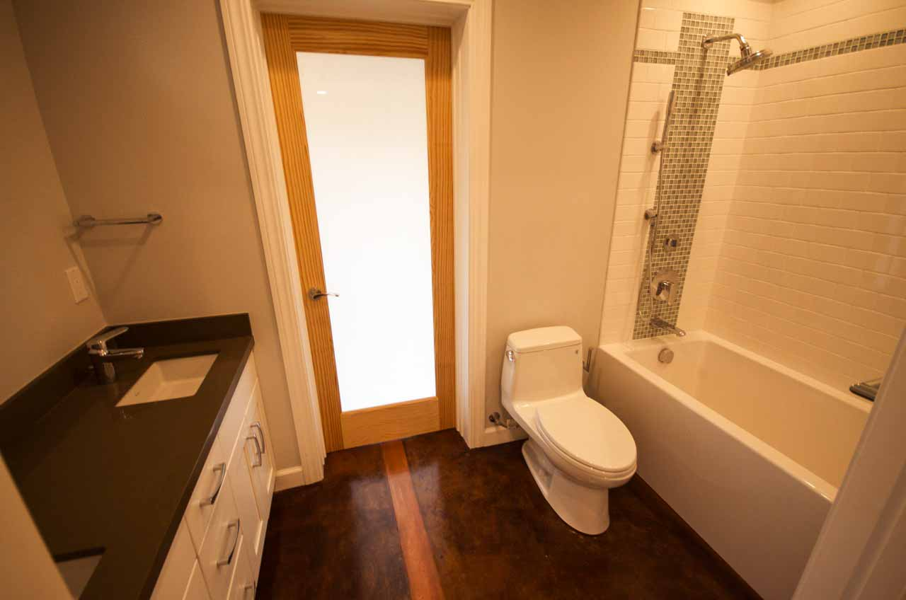 Stained concrete and inlaid wood floor bath