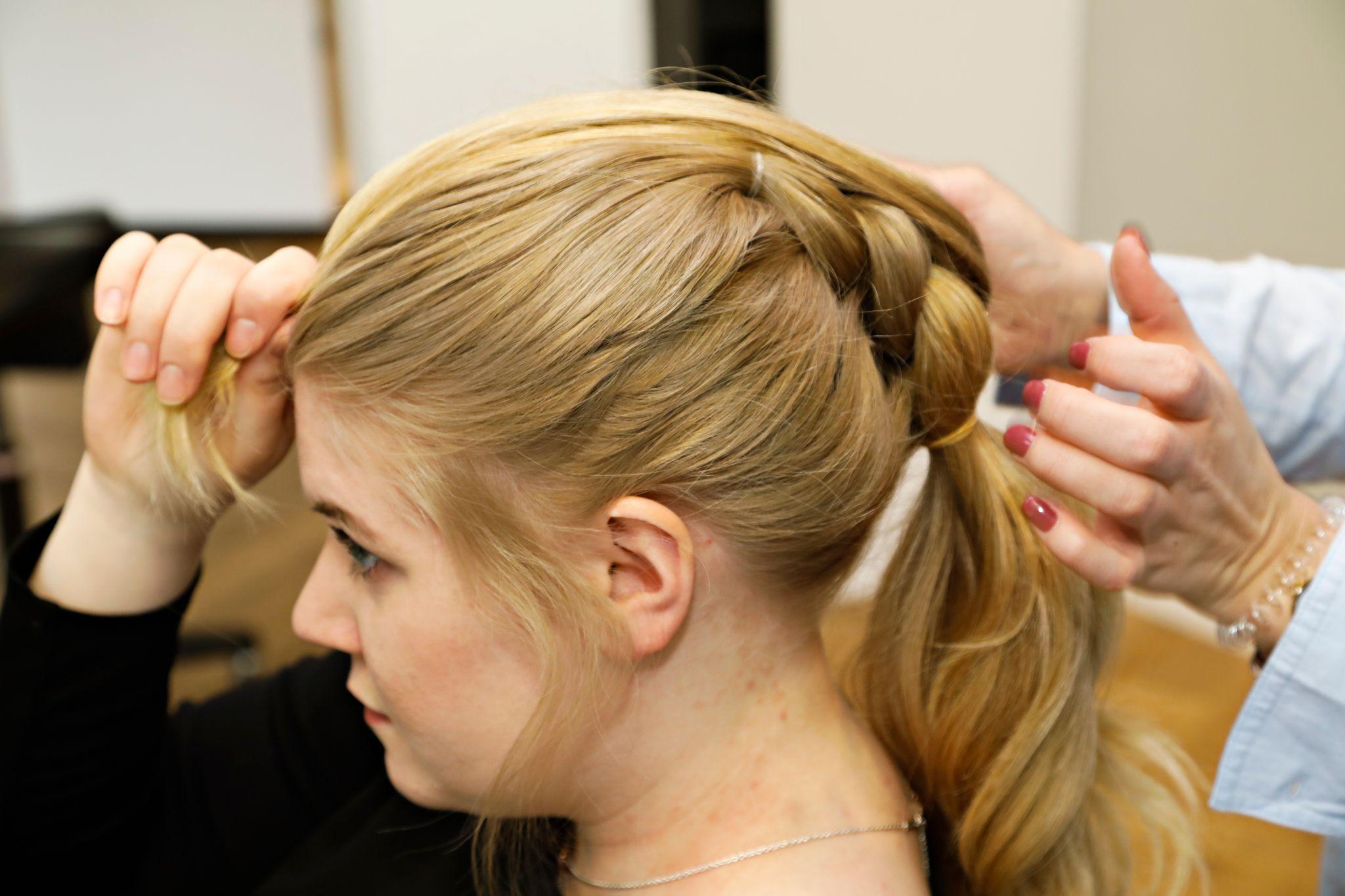 Gjenta prosessen nedover: Del hestehale nummer to i to deler og legg hestehale nummer tre mellom og opp mot ansiktet. Ta opp mer hår fra sidene og fest de to delene med strikk.