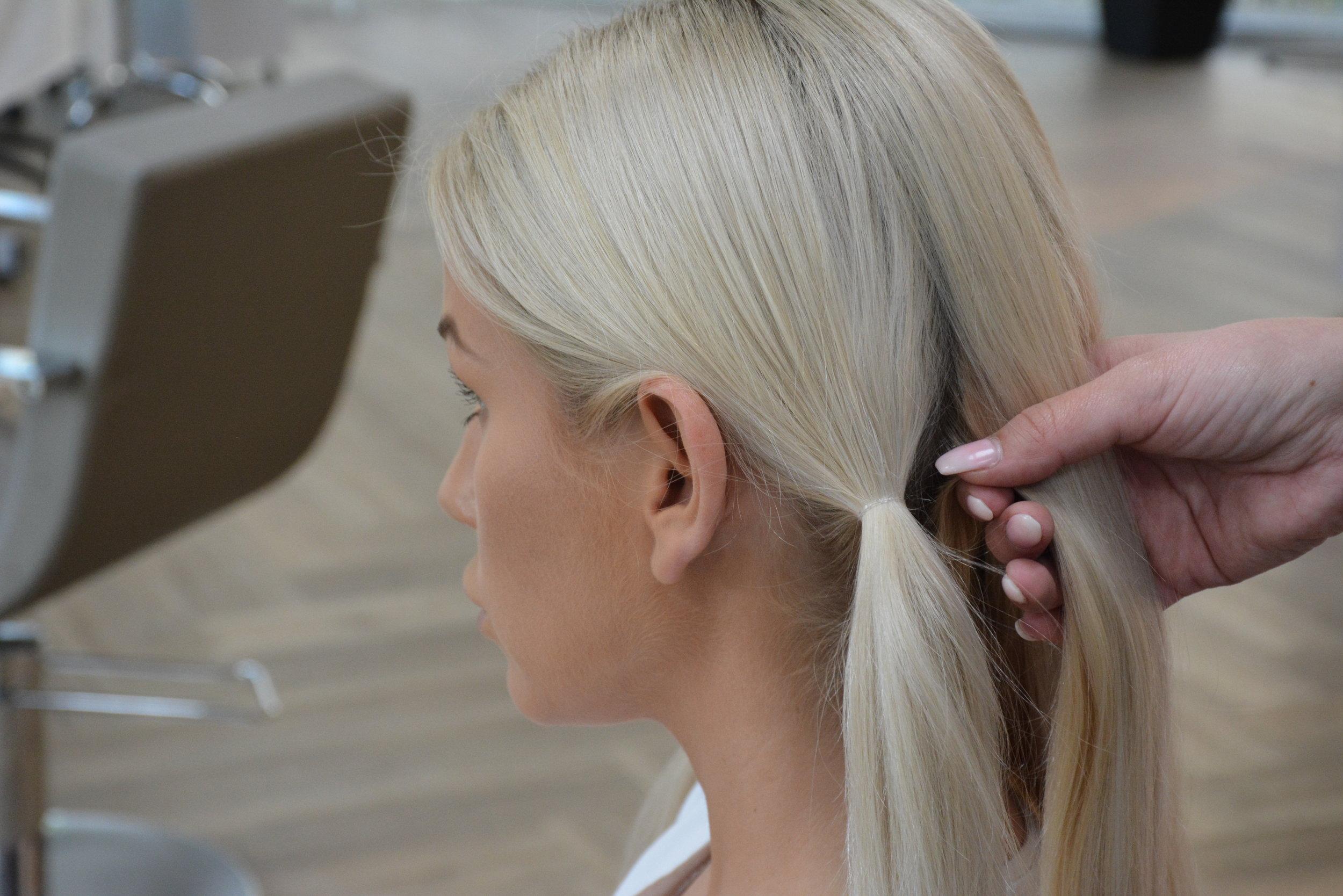 Først må du tupere håret og lage litt volum i skill og bak på hodet. Børst ut slik at det blir fin overflate. Del opp håret og fest en gummistrikk litt bak øret. La det være litt løst hår fremfor øret for et løsere utseende.