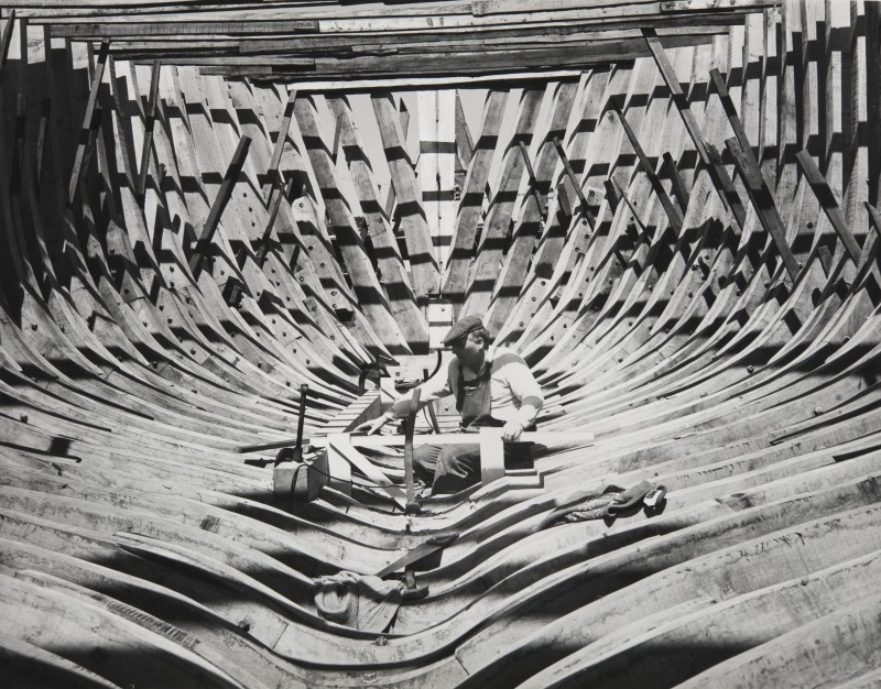 Boat builder within the ribs of a vessel under construction at Anstruther. G.Little 1970