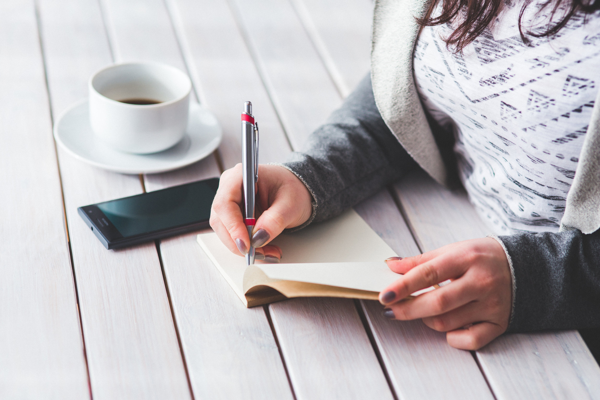 Canva - Woman's hand using a pen noting on notepad.jpg