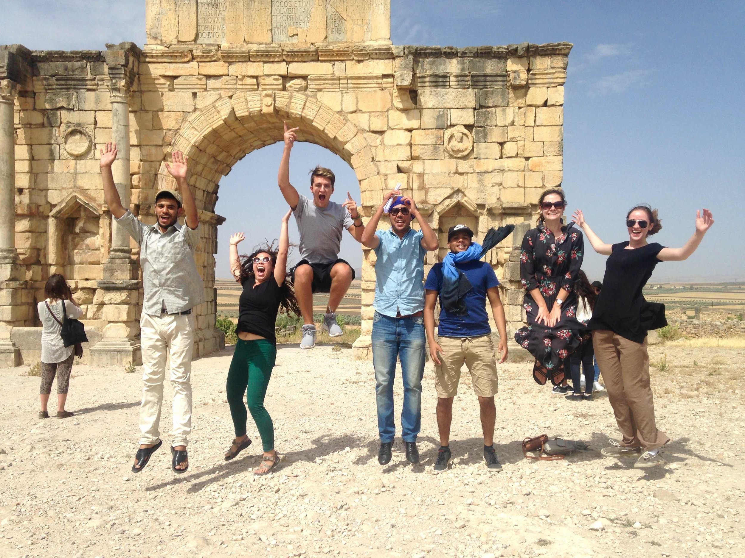 Students, professors, and language partners jump for joy before the entrance of Walili.