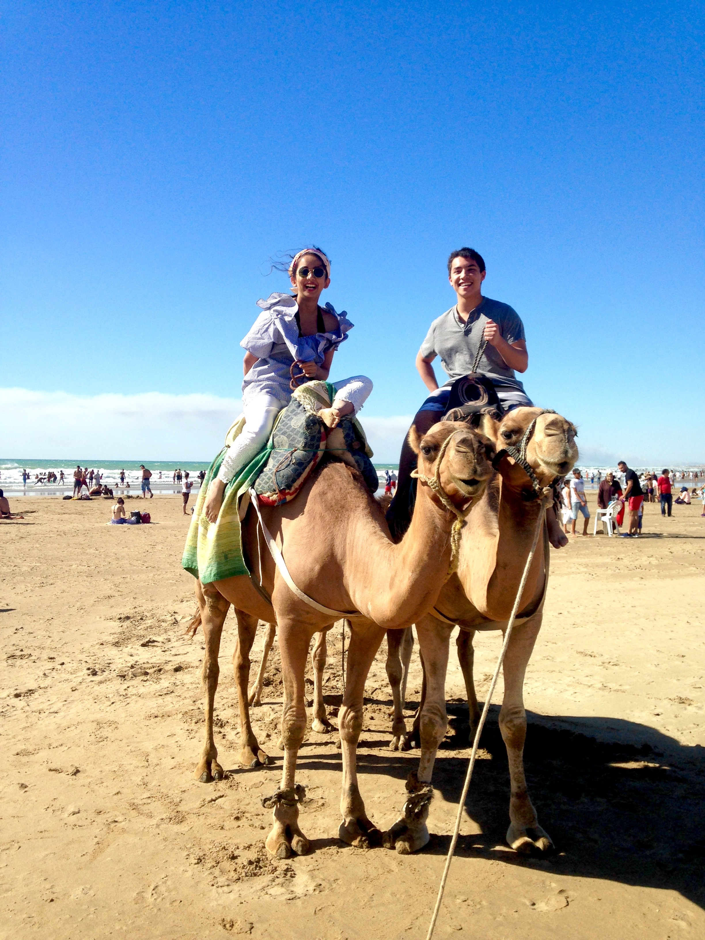 Students Hina Uddin and Alex Yung enjoy a camel ride on the beach.