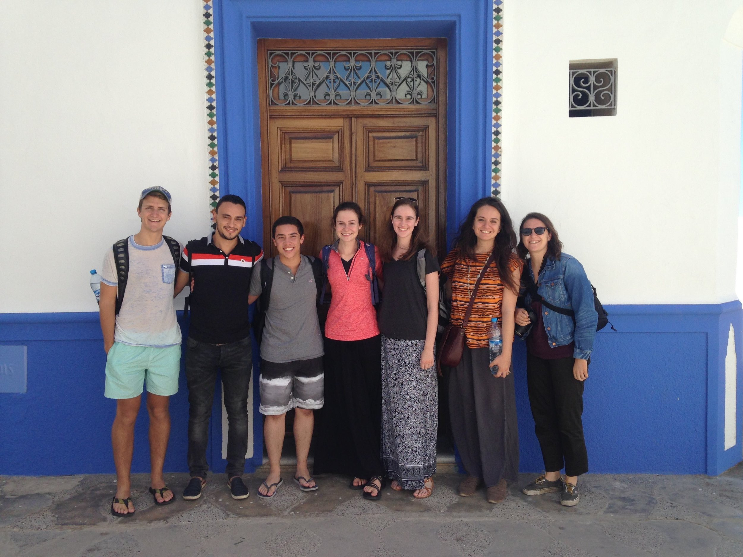 Students smile before one of the many beautiful doors in Asilah.