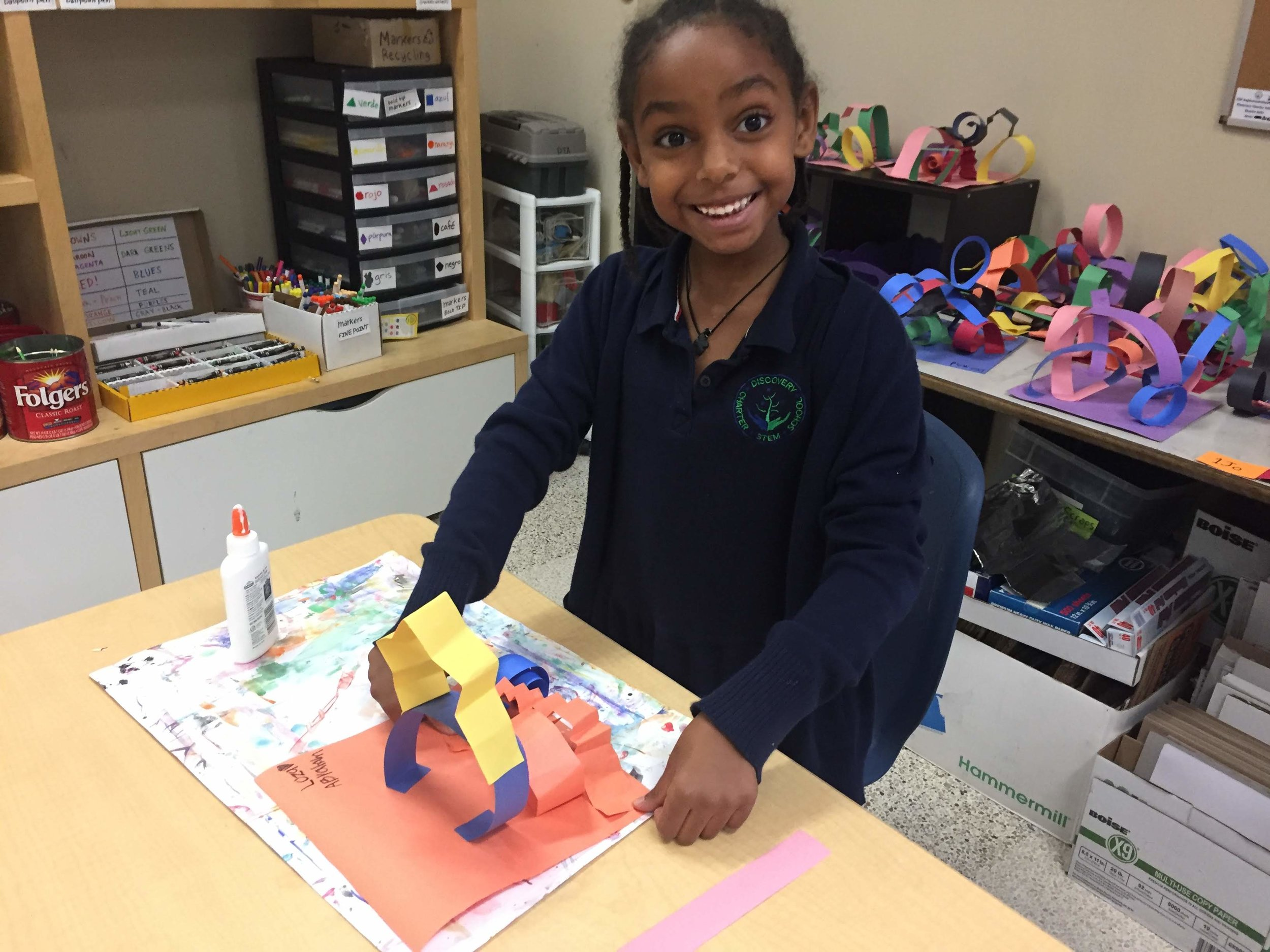 First grade artist, Loza, from Ms. Jacob's class, adds zig-zag lines to her sculpture!
