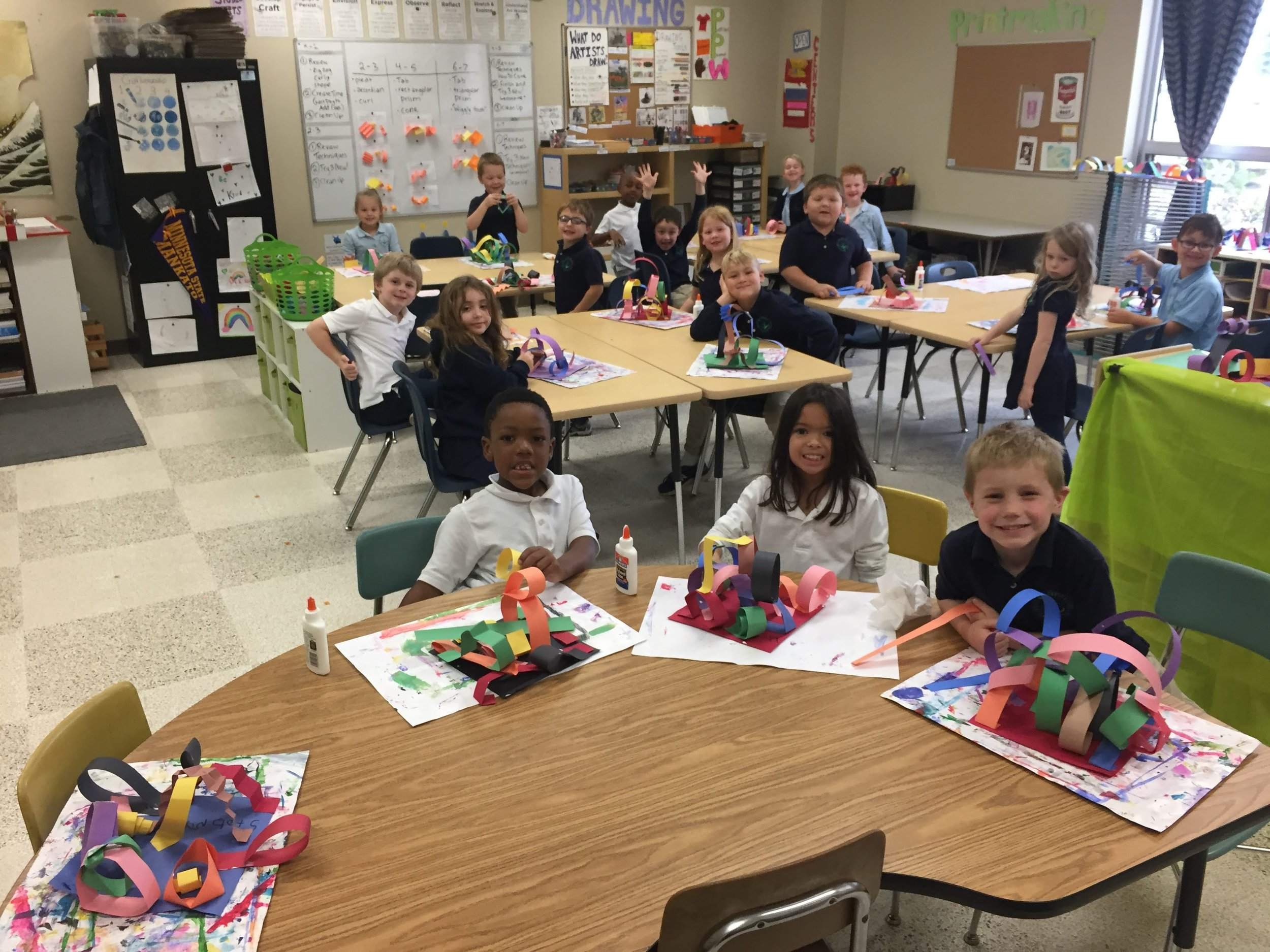 Mrs. Johnson's first grade class takes a moment to smile and show off their sculptures for the camera.