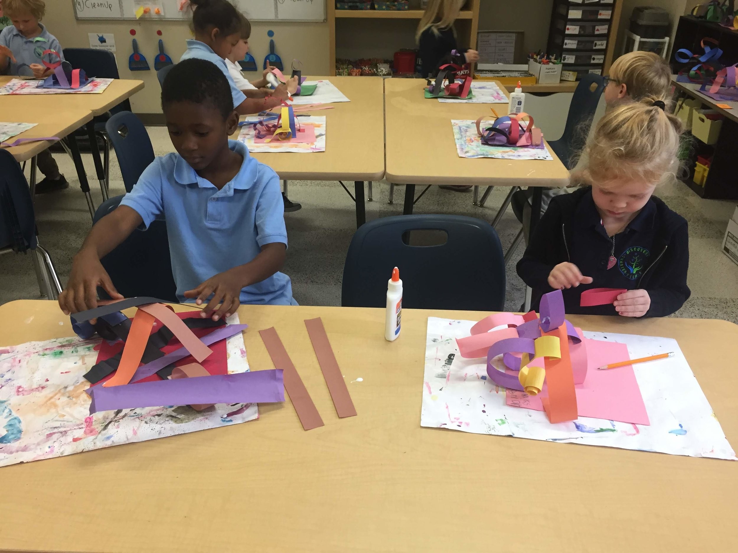 Savion and Briar from Ms. Steven's kindergarten class add to their paper sculptures.