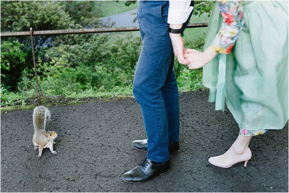 Bride in green dress and groom looking at a squirrel that came over to them in a park in Edinburgh