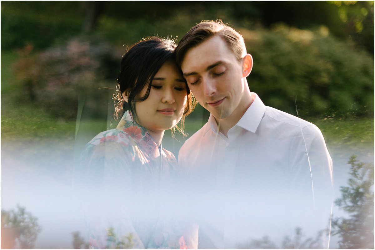 Asian Bride and British groom with their foreheads together with a reflection in a mirror