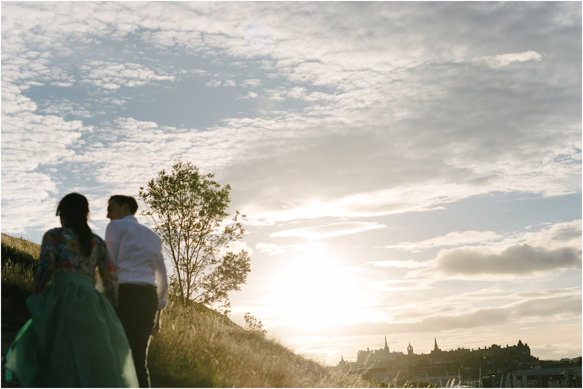 a young couple from the back walking up a hill in Edinburgh in a sunset