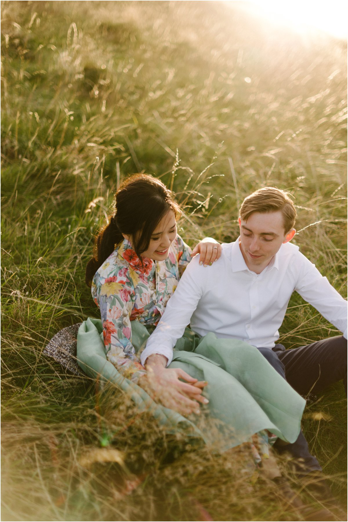 Korean girl and British boy sitting in tall grass holding hands in a sunset