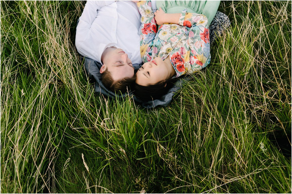Korean girl and British boy sleep hugging in a tall grass in summer