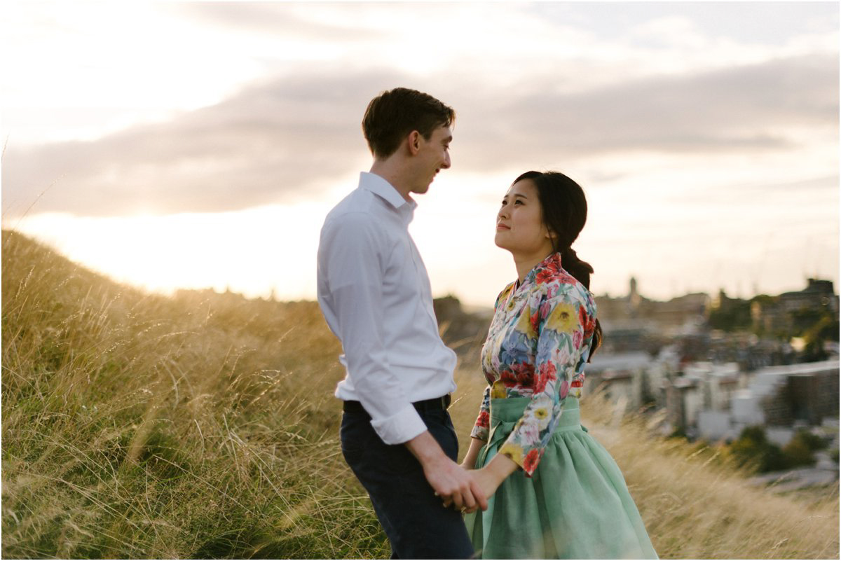 Korean Bride and British groom holding hands on top of Arthur seat in Edinburgh