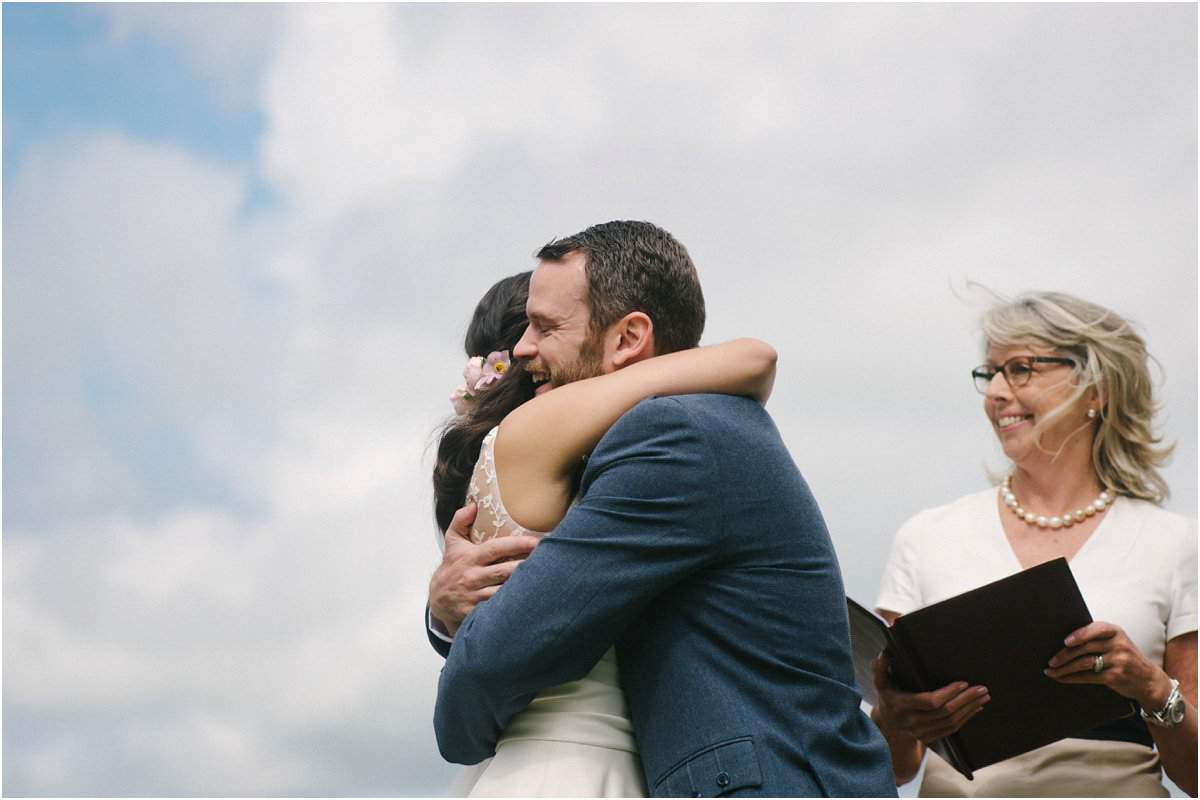 Bride hugs the groom after being pronounced married by their celebrant in an outdoors Summer Scottish castle wedding in Blairquhan by Cro & Kow