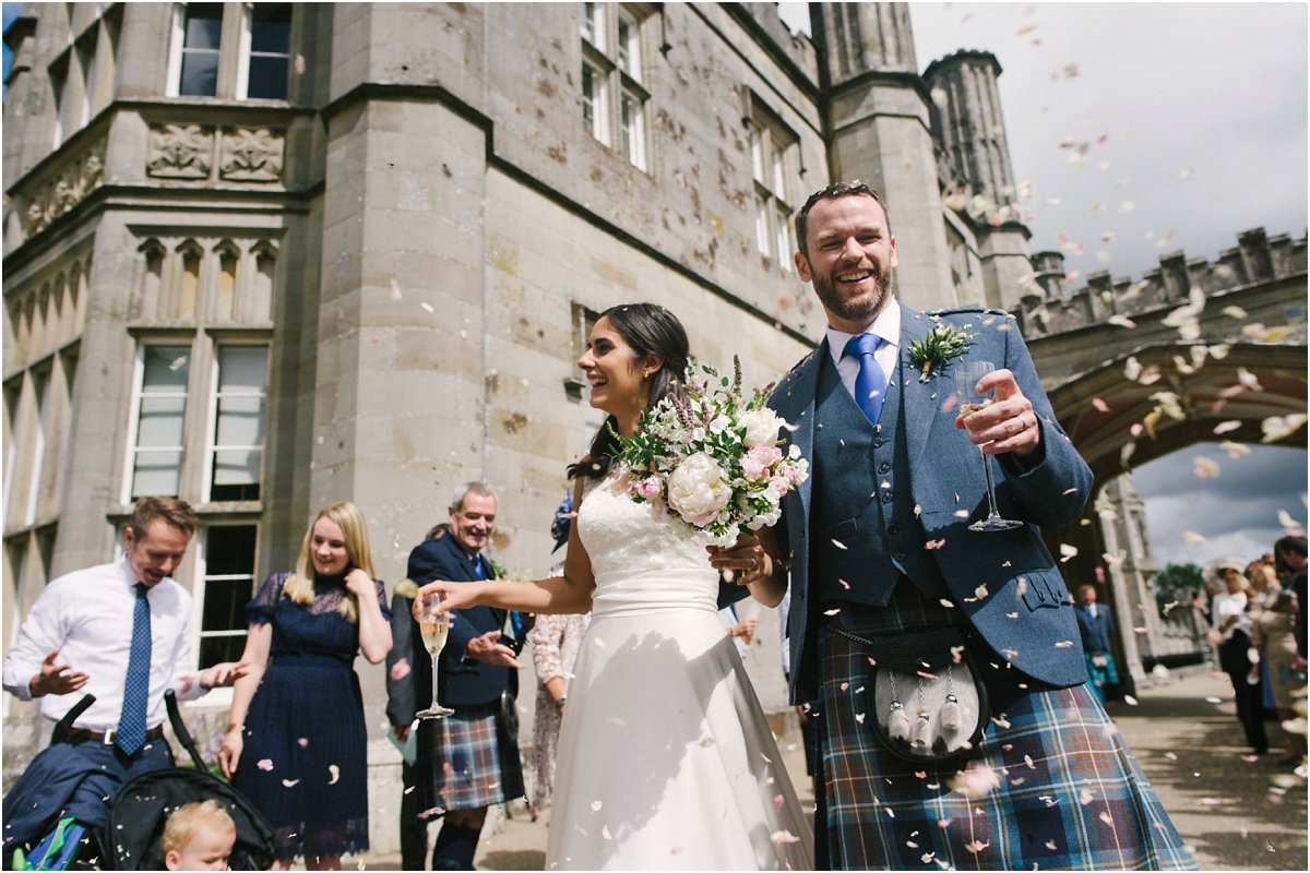 Newlyweds have confetti thrown over them by their guests at a Summer Scottish castle wedding in Blairquhan by Cro & Kow