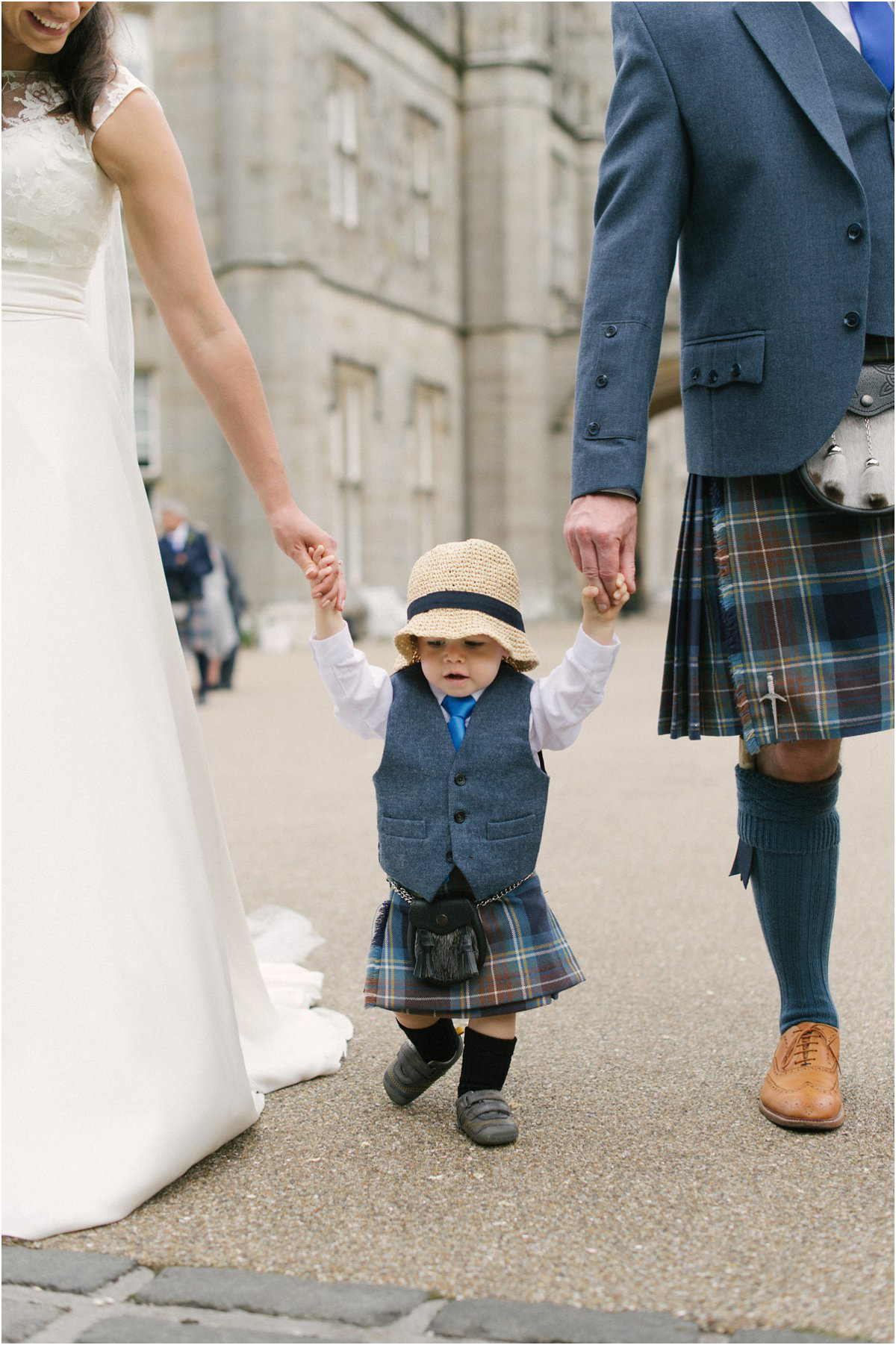 Newlyweds with their young child during their wedding in Blairquhan by Cro & Kow
