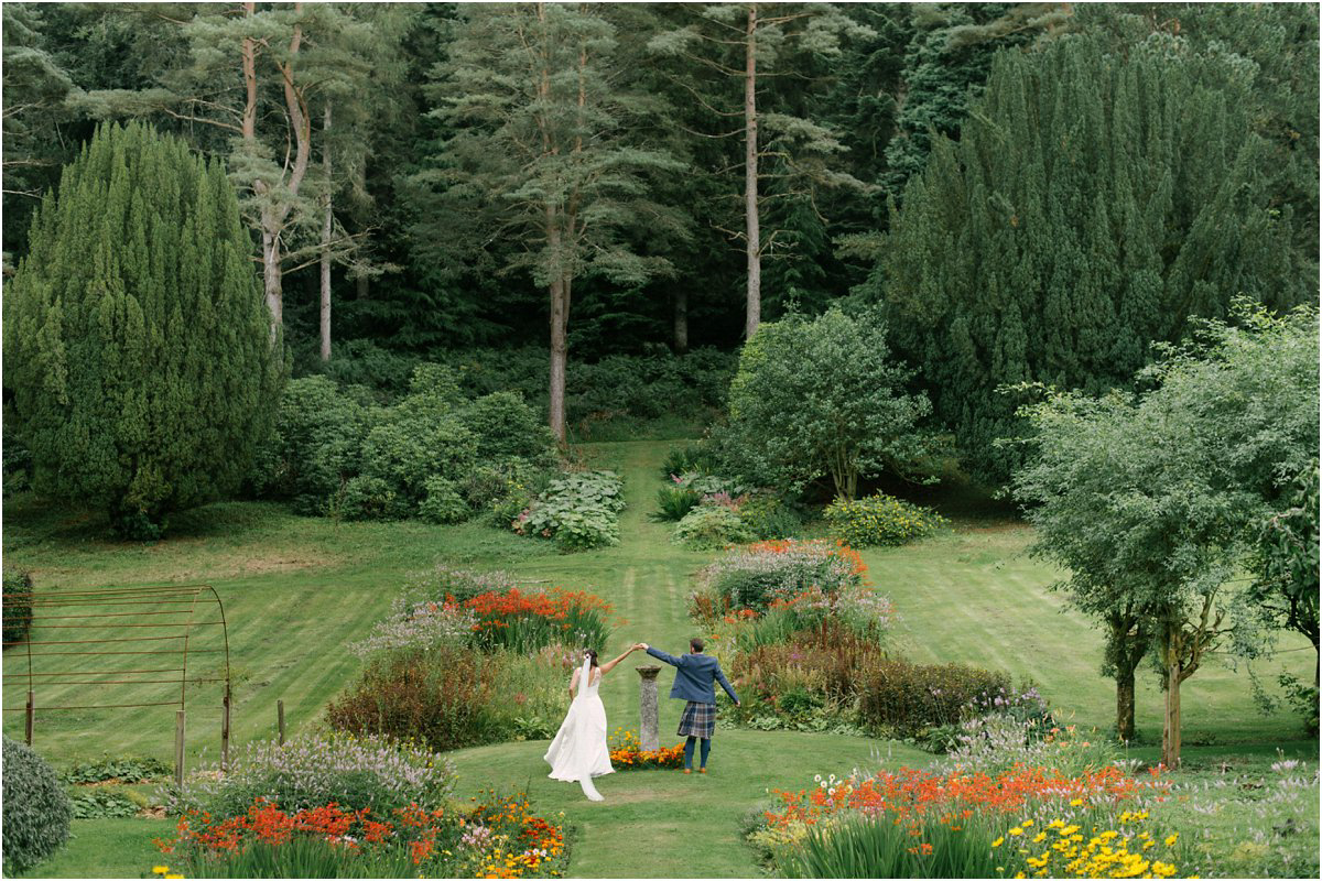 A wedding couple small in a frame when walking in a big garden of Blairquhan castle in Scotland by Cro & Kow