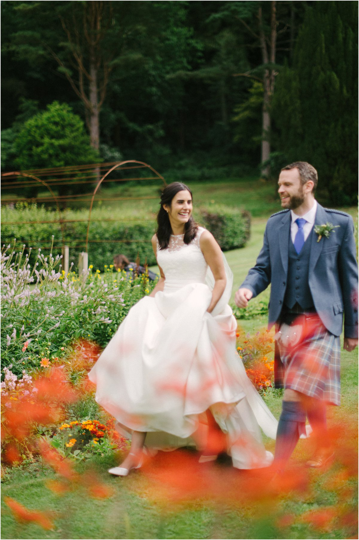 Newly married couple walking among red flowers in a garden of Blairquhan castle in Scotland by Cro & Kow