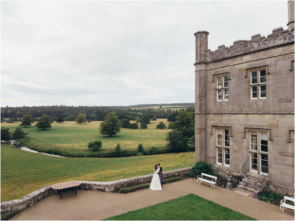Bride and groom admiring landscape in front of a Scottish castle in Blairquhan by Cro & Kow