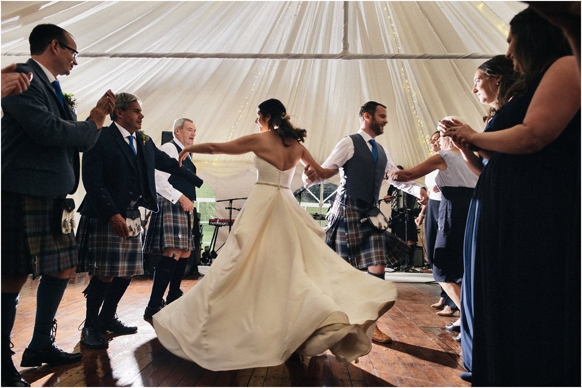 Bride in a big white dress swirling in a ceilidh during a summer Scottish castle wedding in Blairquhan by Cro & Kow