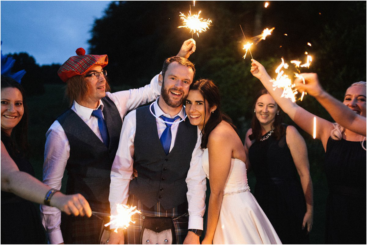 Bride and groom with their wedding party holding sparklers at dusk by Crofts & Kowalczyk Photography