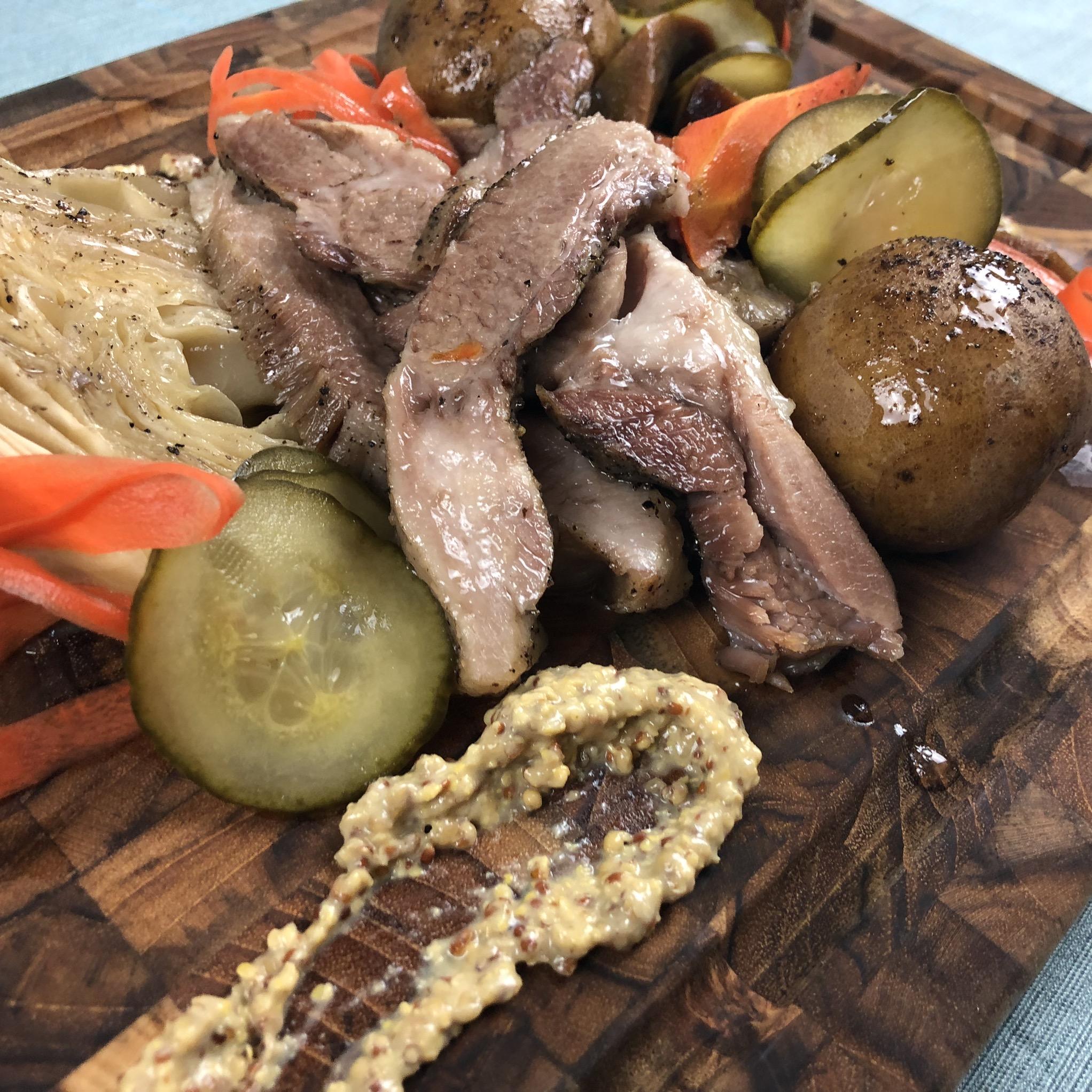Corned Pork Shoulder Steak with vegetables, pickles, and mustard