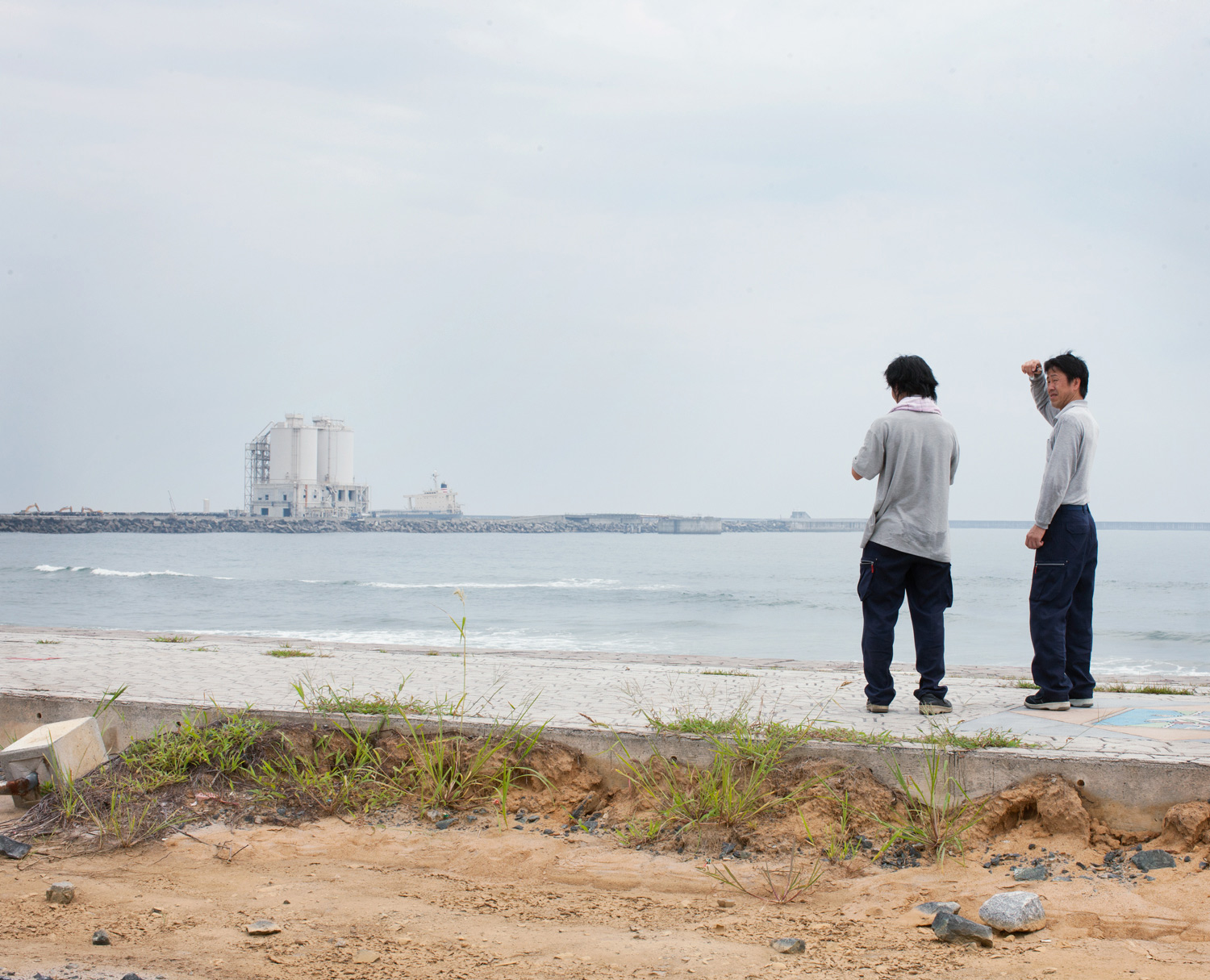 Two men look at the Fukushima Haramachi Thermal Plant
