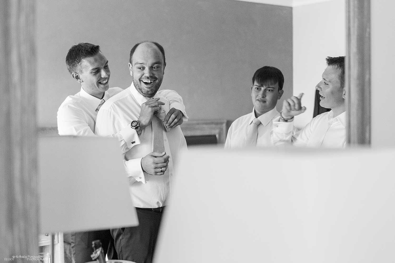 getting-ready-groomsmen-groom-tie-neck-bestman