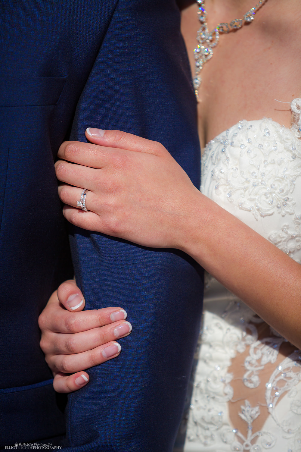 wedding ring detail while bride holds onto grooms arm